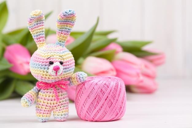 Gehaakt konijn met delicate roze tulpen. pasen concept. gebreid speelgoed, handgemaakt, handwerk, amigurumi.