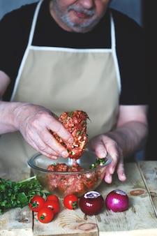 Gehakt in een kom en de kok