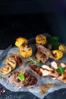 Gehakt kippenvlees, varkensvlees en rundvlees met maïs, kruiden op papier op een donkere achtergrond