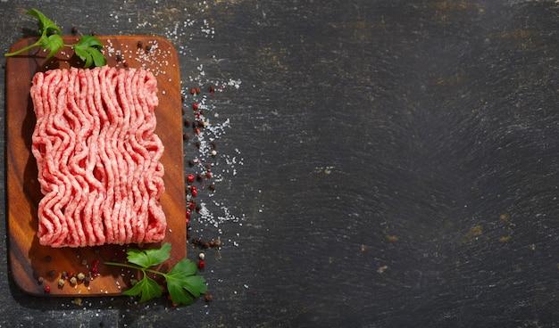 Gehakt met ingrediënten voor het koken op een houten bord, bovenaanzicht