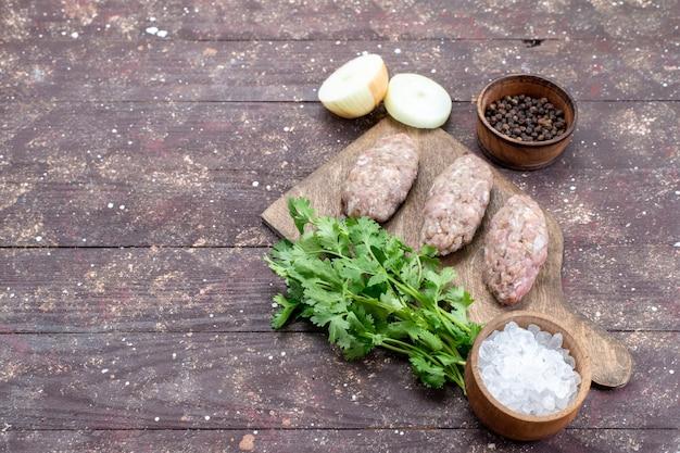 Gehakt rauw vlees kotelet gevormd met greens uien zout op bruin bureau