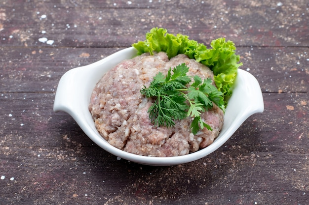 Gehakt rauw vlees met greens binnen plaat op bruin