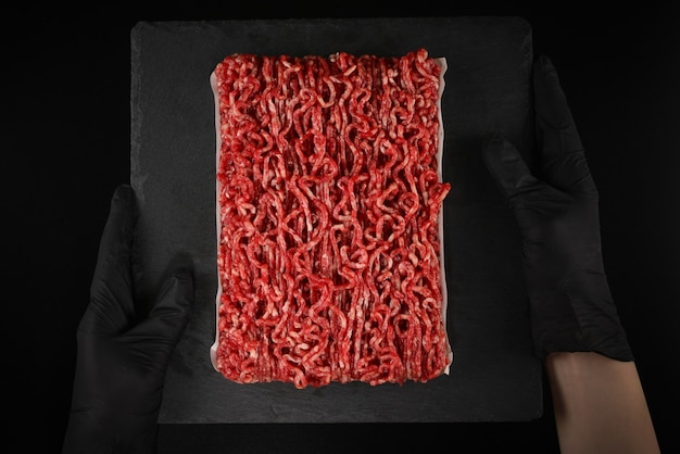 Gehakt rauw vlees op een zwarte achtergrond in handen van de vrouw.