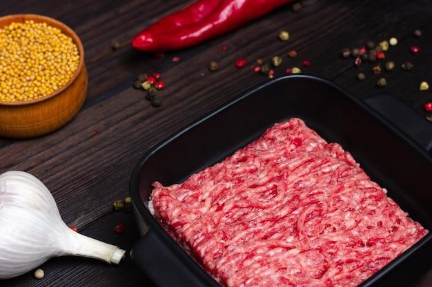 Gehakt varkensvlees in een zwarte plaat op een houten tafel, samen met kruiden en paprika, cherrytomaatjes par...