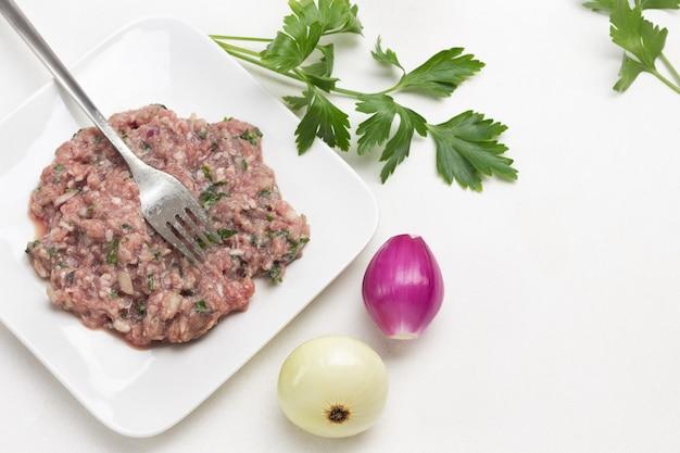 Gehakt vlees en vork op plaat. gepelde uien en takje peterselie op tafel. witte achtergrond. bovenaanzicht