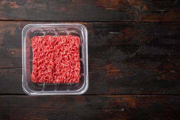 Gehakt vlees in plastic container set, op oude donkere houten tafel, bovenaanzicht plat lag