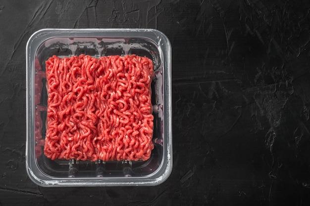Gehakt vlees in plastic container set, op zwarte stenen tafel, bovenaanzicht plat lag