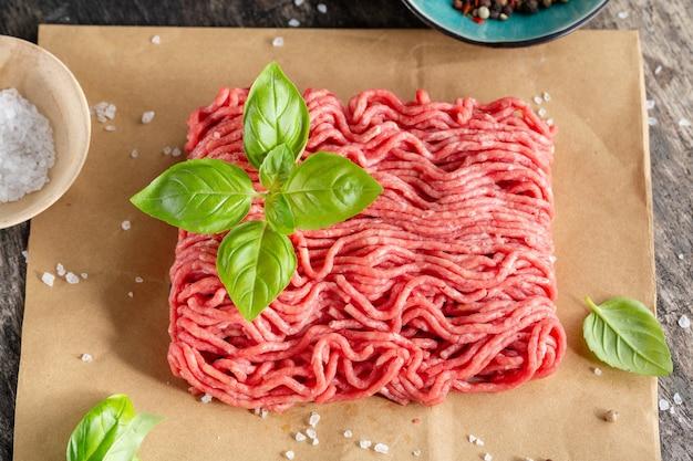 Gehakt vlees met kruiden op papier op tafel. detailopname