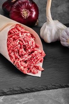 Gehakt vlees rundvlees als gedetailleerde close-up shot op donkere houten achtergrond.