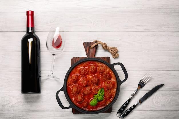 Gehaktballen in tomatensaus in een koekenpan met een fles wijn, twee glazen, mes en vork op een witte houten bord