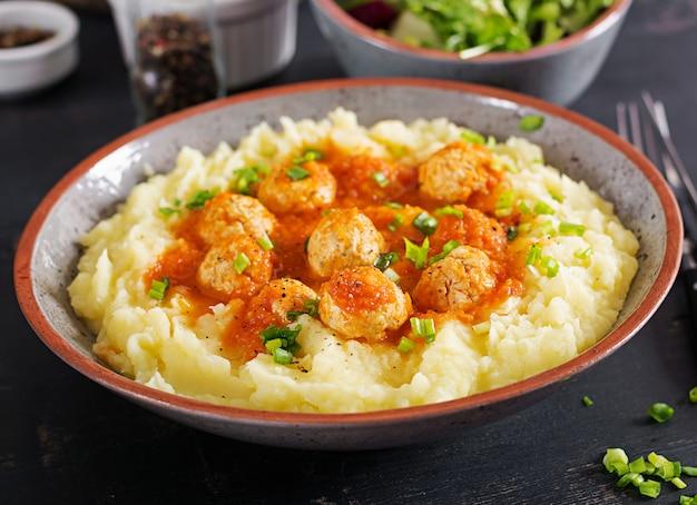 Gehaktballen in tomatensaus met aardappelpuree in kom.