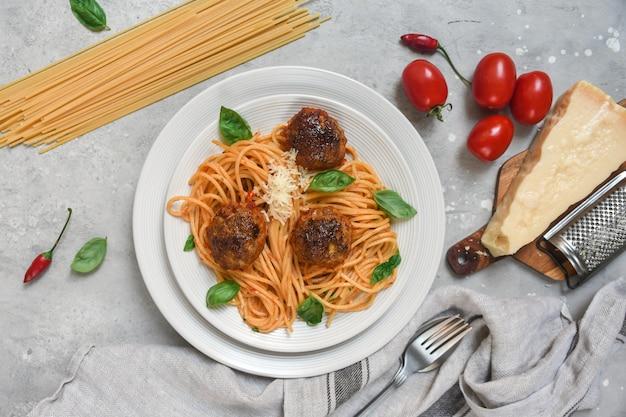Gehaktballen in tomatensaus met pasta spaghetti op witte plaat op lichte stenen tafel. bovenaanzicht
