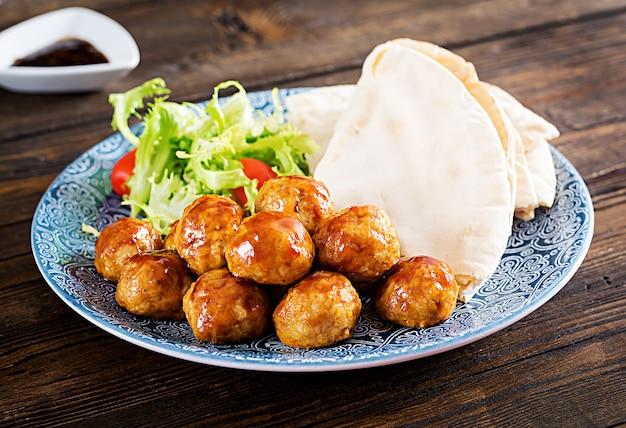 Gehaktballen in zoetzure glazuur op een bord met pitabrood en groenten in een marokkaanse stijl
