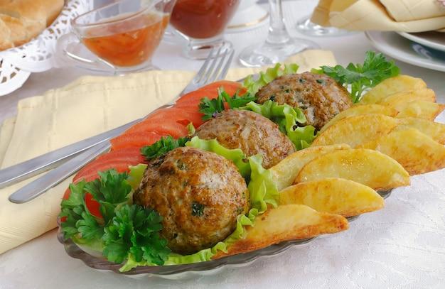 Gehaktballen met greens op slabladeren met aardappelen en tomaten
