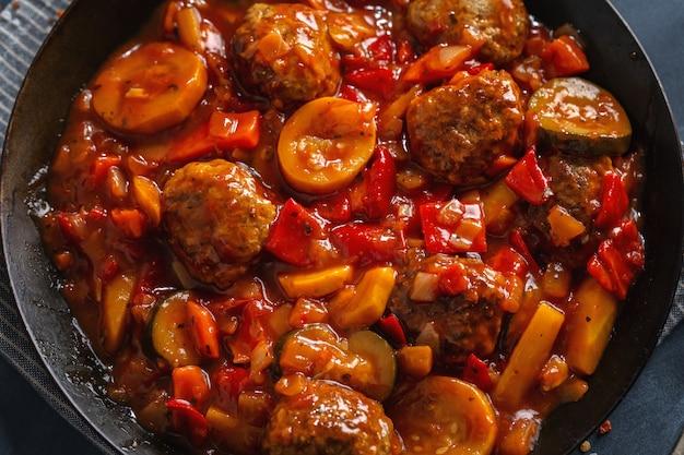 Gehaktballen met groenten en saus gemaakt in de pan en geserveerd op tafel.