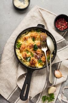 Gehaktballen met kaas en roomsaus in gietijzeren pan op grijs vintage oppervlak. bovenaanzicht