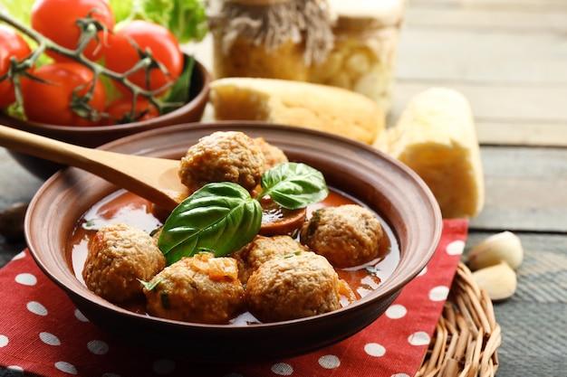 Gehaktballen met tomatensaus, houten lepel op houten