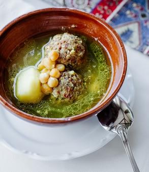 Gehaktballensoep in bouillon met aardappelen, bonen en kruiden.