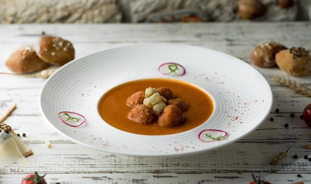 Gehaktballensoep met kruiden en tomatensaus in witte plaat met broodjes.