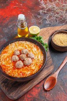 Gehaktballensoep met noedels aan boord en ongekookte pasta's, citroengroenten op donkere achtergrondbeelden