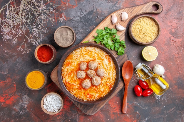 Gehaktballensoep met noedels aan boord van ongekookte pasta's, citroengroenten, oliefleslepel en verschillende kruiden op donkere tafel