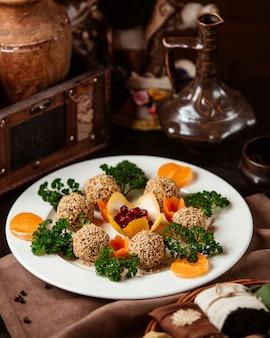 Gehaktballetjes in sesamzaadjes met decorkruiden worteltjes en mandarijn schijfjes