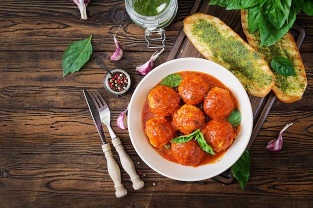 Gehaktballetjes in tomatensaus en toast met basilicumpesto.