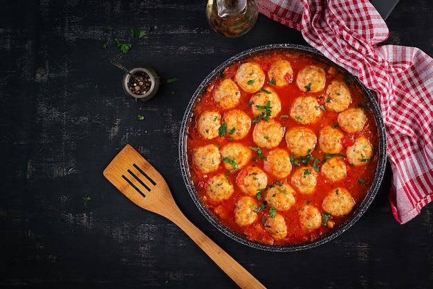Gehaktballetjes in tomatensaus in een koekenpan op donkere achtergrond. bovenaanzicht, plat gelegd.