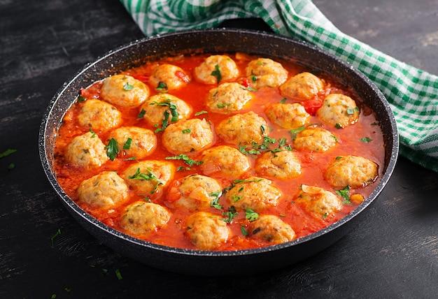 Gehaktballetjes in tomatensaus in een koekenpan op donkere achtergrond.