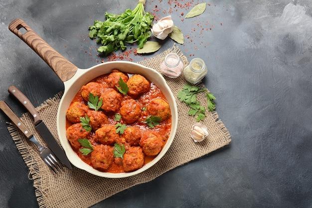 Gehaktballetjes in zoete tomatensaus met kruiden geserveerd in een koekenpan