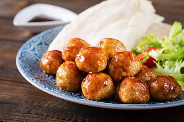 Gehaktballetjes in zoetzure glazuur op een bord met pitabroodje en groenten in een marokkaanse stijl op een houten tafel.