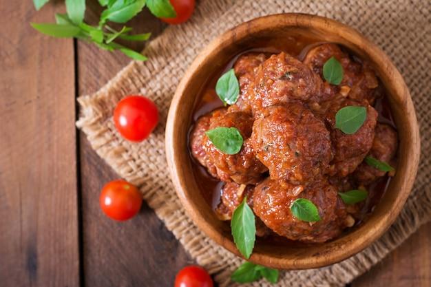 Gehaktballetjes in zoetzure tomatensaus en basilicum in een houten kom