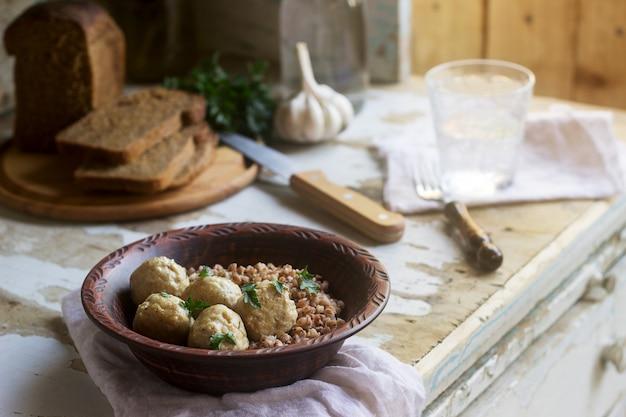 Gehaktballetjes in zure roomsaus, geserveerd met boekweitpap, brood en knoflook. rustieke stijl.