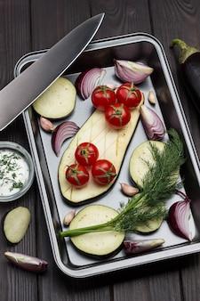 Gehakte aubergines, uienpartjes, takje dille op pallet. keukenmes op pallet. bovenaanzicht