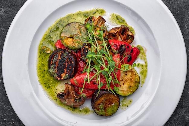 Gehakte gebakken gegrilde groenten met champignons, courgette, aubergines, paprika, champignons, op een wit bord met saus
