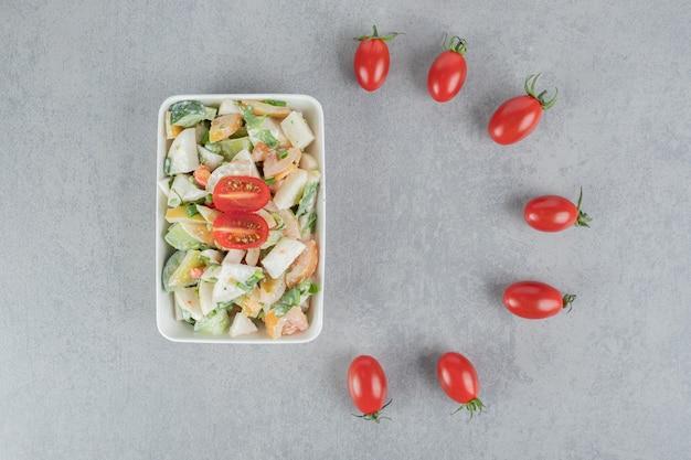 Gehakte groene tomatensalade met kruiden en specerijen op betonnen ondergrond