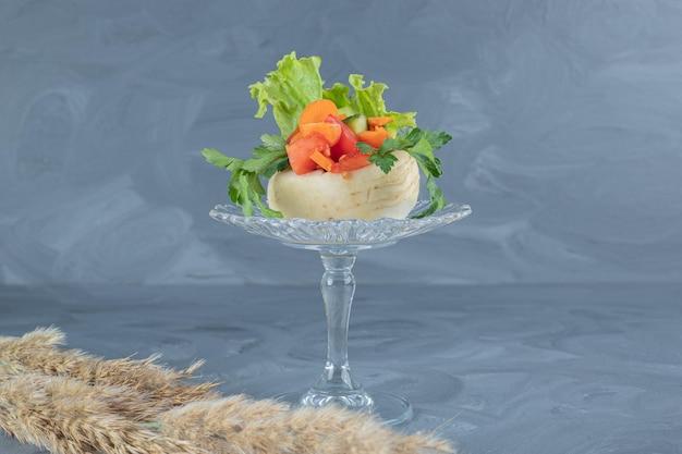 Gehakte groenten bovenop een witte raap op een glazen voetstuk met stengels van naaldgras op marmeren tafel.