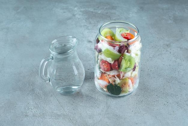 Gehakte groenten in glazen pot met water.