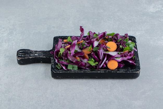 Gehakte groentesalade in de houten plank, op het marmer.