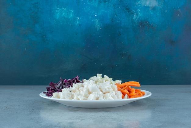 Gehakte groentesalade in een witte schotel.
