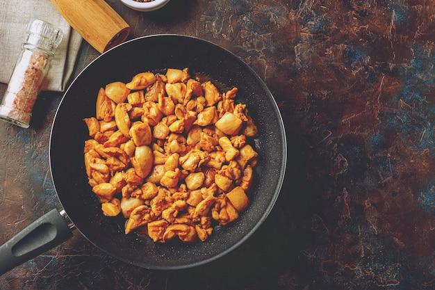 Gehakte kipfilet gebakken op koekenpan op donkere tafel, bovenaanzicht. aziatische stijl.
