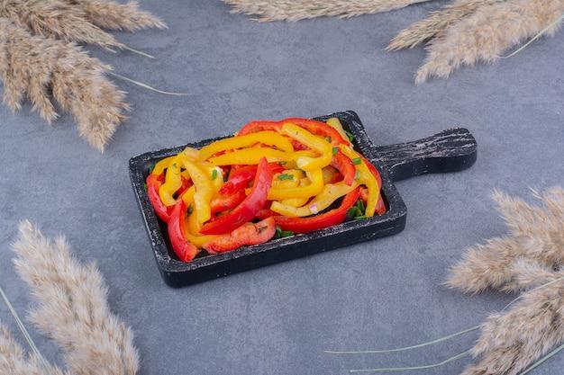 Gehakte kleurrijke paprikasalade in een houten schotel