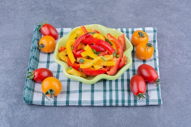 Gehakte kleurrijke paprikasalade met cherrytomaatjes opzij
