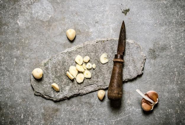 Gehakte knoflook en oud mes op een stenen standaard