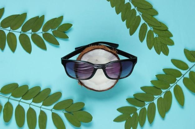 Gehakte kokosnoot met zonnebril op blauwe achtergrond met groene bladeren