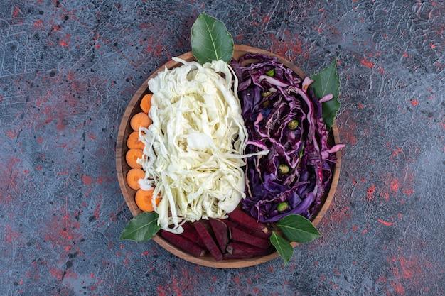 Gehakte rode en witte kool, bieten en wortelen op een dienblad op zwarte tafel.