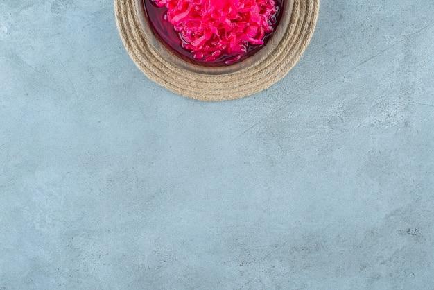 Gehakte rode gefermenteerde zuurkool in een kom op een onderzetter, op de blauwe tafel.