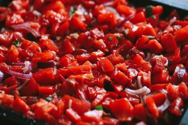 Gehakte rode tomaten met kruiden in een zwarte pan