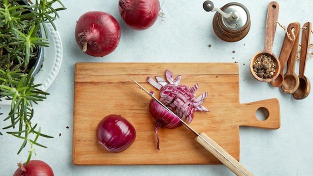 Gehakte rode uien op houten snijplank, bovenaanzicht