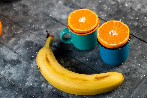 Gehakte sinaasappelen en bananen op een houten tafel